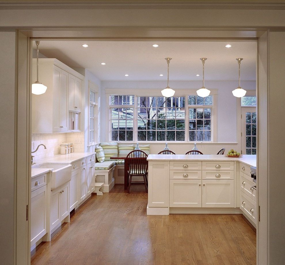 High Hat Lights with Traditional Kitchen Also Apron Sink Banquette Seating Bench Seat Eat in Kitchen Farm Sink Frame and Panel Cabinets Kitchen Island Natural Wood Pendant Lights Spindle Chairs White Counters White Painted Wood Wood Floor