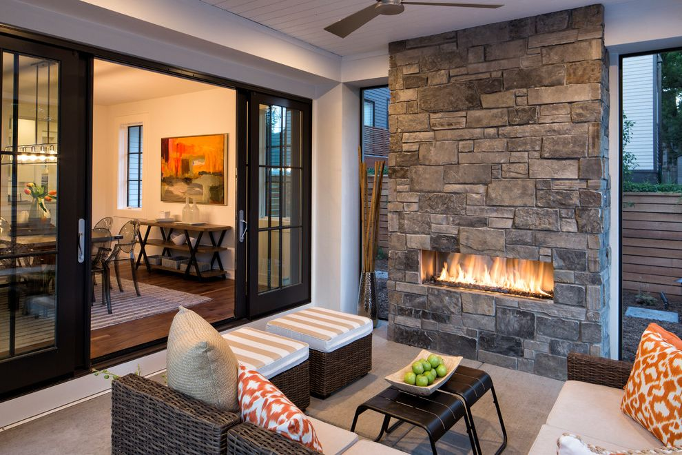 Highmark Seating   Transitional Patio  and Black Sliding Doors Indoor Outdoor Orange Pillow Outdoor Seating Stacked Stone Fireplace Wicker Ottoman Wicker Sectional