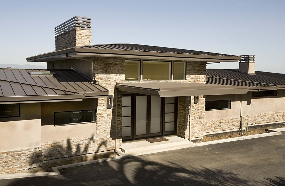 Hip Roof Construction   Contemporary Exterior  and Chimney Concrete Paving Driveway Entrance Entry French Doors Front Door Frosted Glass Glass Doors Metal Roof Neutral Colors Outdoor Lighting Overhang Porch Sconce Stacked Stone Stone Wall Wall Lighting