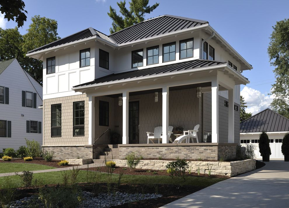 Hip Roof Construction with Transitional Exterior  and Adirondack Brick Foundation Columns Covered Porch Lawn Metal Roof Pendant Lights Stone Garden Wall