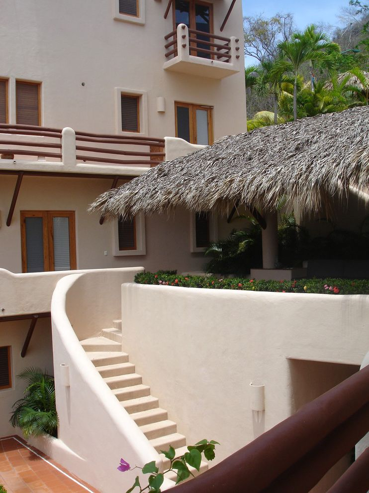 House of Tropicals   Tropical Exterior Also Balcony Beachfront Beige House Condominium Courtyard Covered Patio Indoor Outdoor Outdoor Staircase Stucco Thatch Roof Tropical House Tropical Landscaping Wood Railing