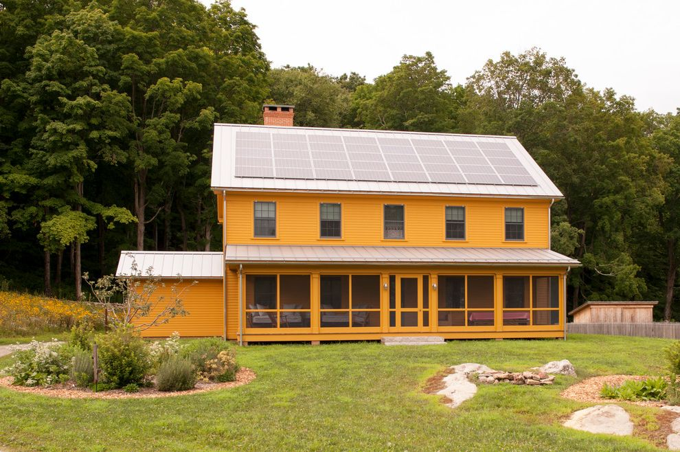 How Much Does Solar Panels Cost   Farmhouse Exterior  and Brick Chimney Gable Roof Large Porch Metal Roofs Orange House Reclaimed Granite Steps Screen Door Screen Porch Solar Panels Standing Seam Metal Roof Traditional House Paint Yellow House