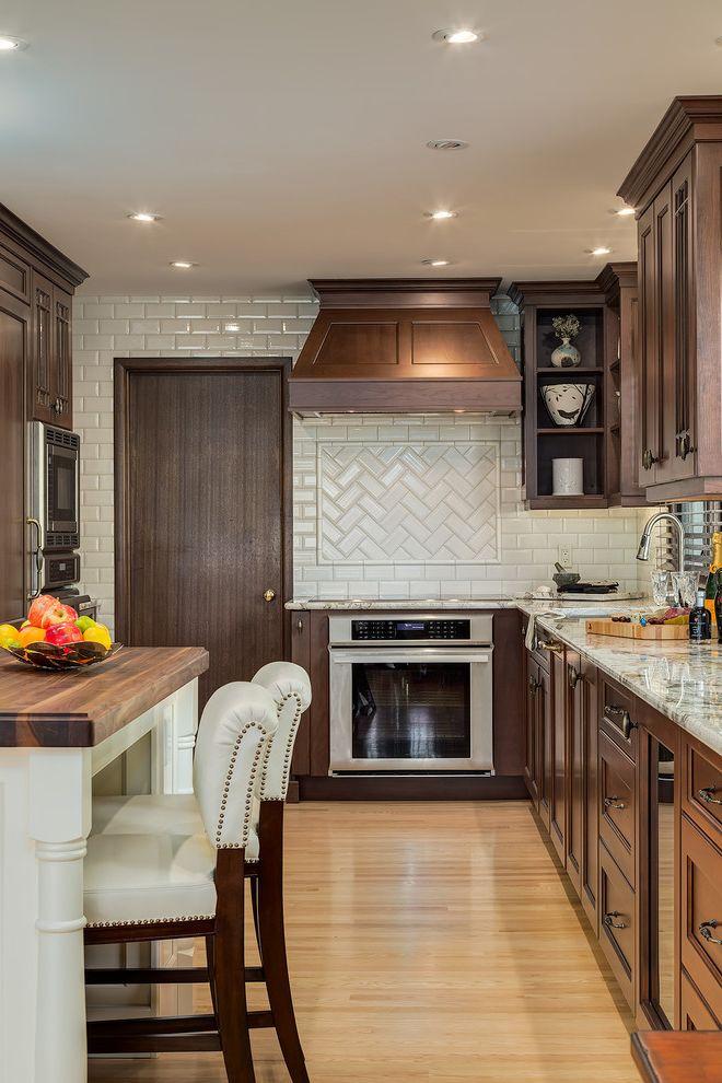 How to Bevel Wood with Traditional Kitchen  and Dark Wood Door Herringbone Subway Tile Nailhead Trim Recessed Lighting White Bar Stools White Countertop Wood Countertop