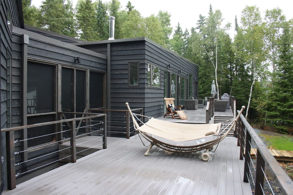 How to Build a Composite Deck   Modern Deck  and Birch Trees Black Cable Rails Charcoal Gray Cottage Deck Deck Chair Evergreen Trees Glass Doors Hammock Modern Deck Siding