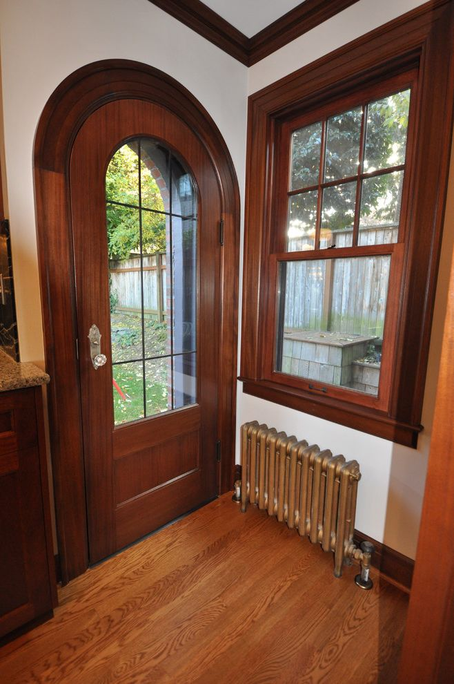How to Change a Door Knob   Traditional Entry Also Arch Door Crown Molding Curved Door Dark Wood Dark Wood Crown Molding Dark Wood Trim Door with Glass Window Lead Glass Door Mahogany Radiator White Wall and Dark Wood