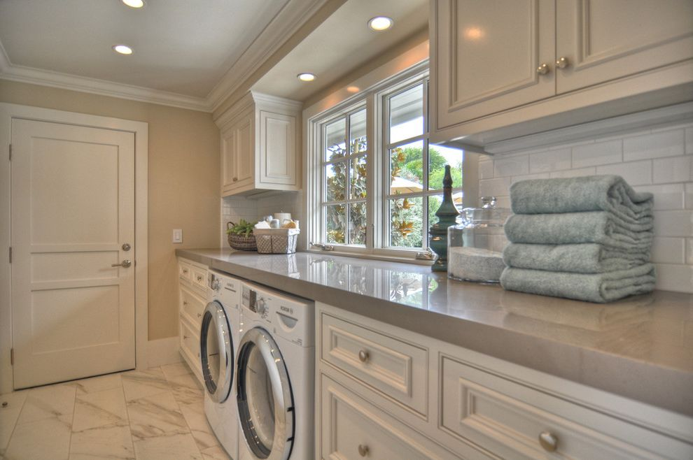 How to Clean Front Load Washer   Beach Style Laundry Room Also Built in Storage Ceiling Lighting Front Load Washer and Dryer Monochromatic Neutral Colors Recessed Lighting Subway Tiles Tile Backsplash Tile Flooring White Cabinets White Wood Wood Trim
