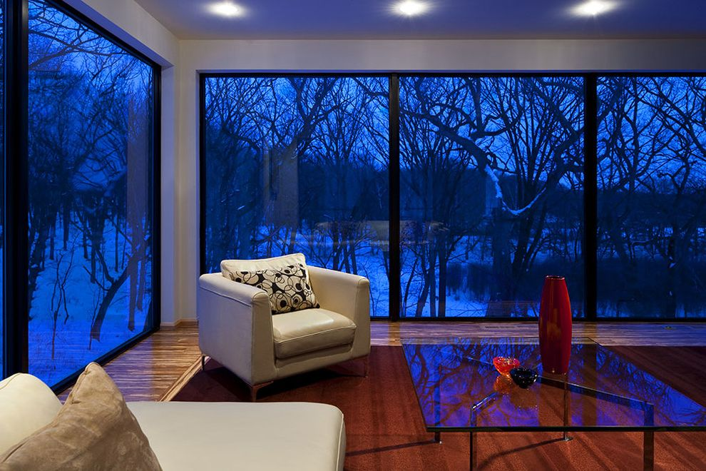 How to Insulate Windows for Winter   Modern Living Room Also Accent Chair Ceiling Lighting Corner Windows Glass Coffee Table Glass Walls Leather Armchair Minimal Neutral Colors Recessed Lighting Seasonal Snow View Winter Wood Flooring