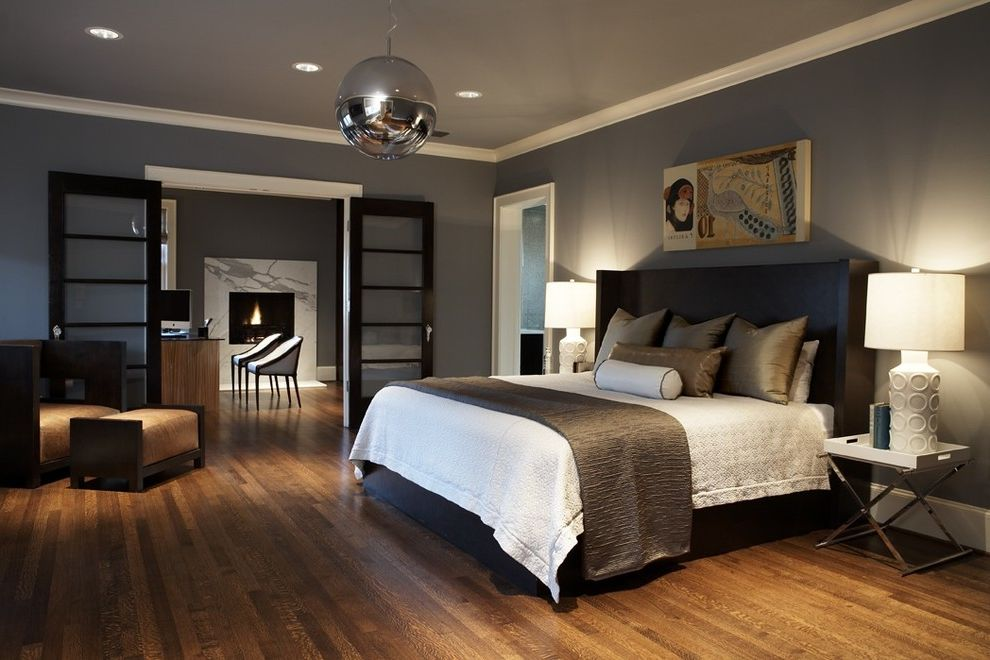 How to Make Your Bedroom Cozy   Contemporary Bedroom  and Arm Chair Chrome Crown Molding Dark Stain Fire Surround Fireplace French Doors Gray Lamp Master Suite Mirror Ball Ottoman Quilt Recessed Lighting Side Table Silk Taupe White Wood Floor