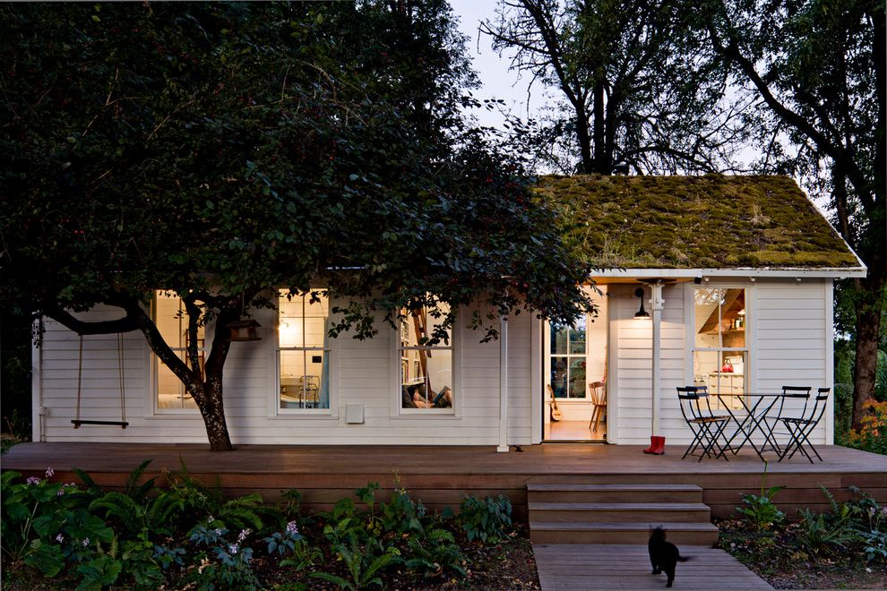 How to Reduce Dust in My House   Farmhouse Exterior Also 2 Over 2 Windows Bistro Chairs Bistro Table Cat Charming Curb Appeal Deck Front Porch Green Roof Moss Roof Slender Columns Small House Swing Tiny House White Siding