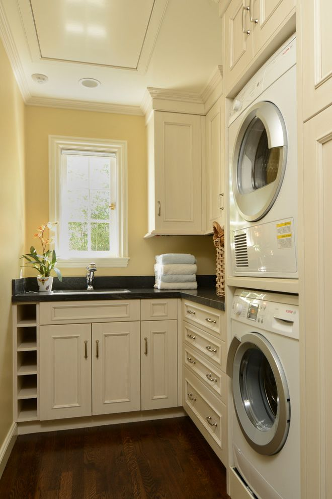 How to Stack a Washer and Dryer   Craftsman Laundry Room Also Built in Storage Casement Windows Crown Molding Small Space Stackable Washer and Dryer Stacked Washer and Dryer White Cabinets White Trim Wood Floors Yellow Walls