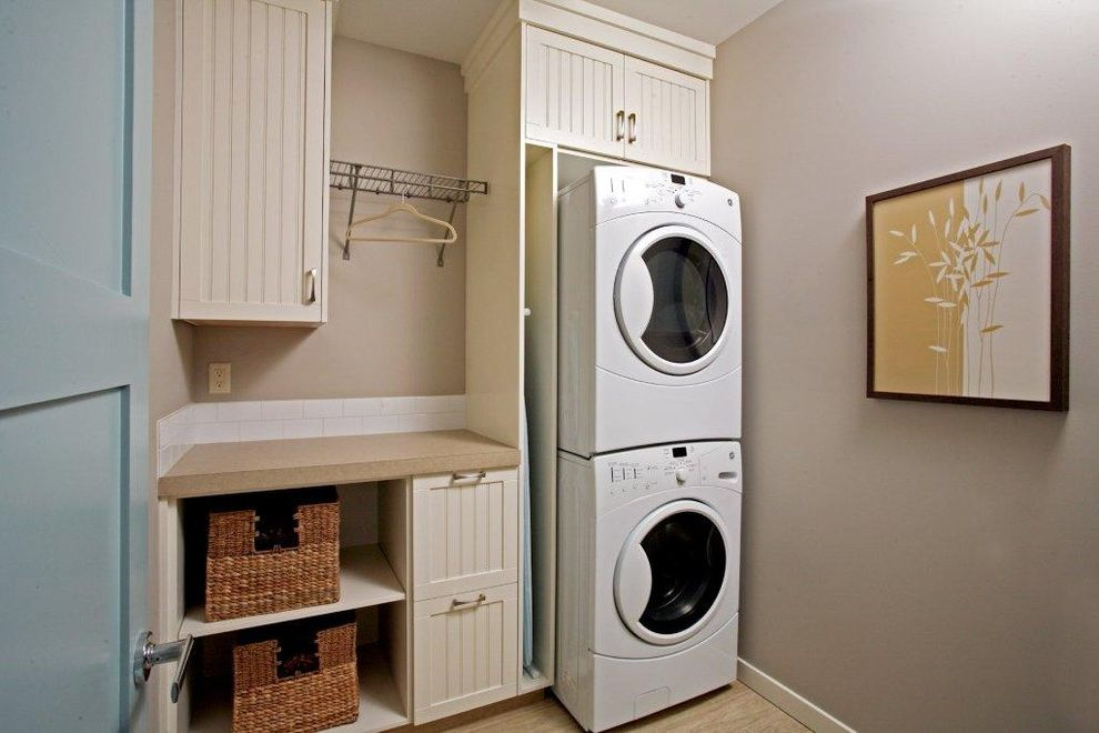 How to Stack a Washer and Dryer   Traditional Laundry Room  and Artwork Beadboard Cabinets Dryer Rack Front Loading Washer and Dryer Stackable Washer and Dryer Stacked Washer and Dryer Storage Baskets Wall Art Wall Decor