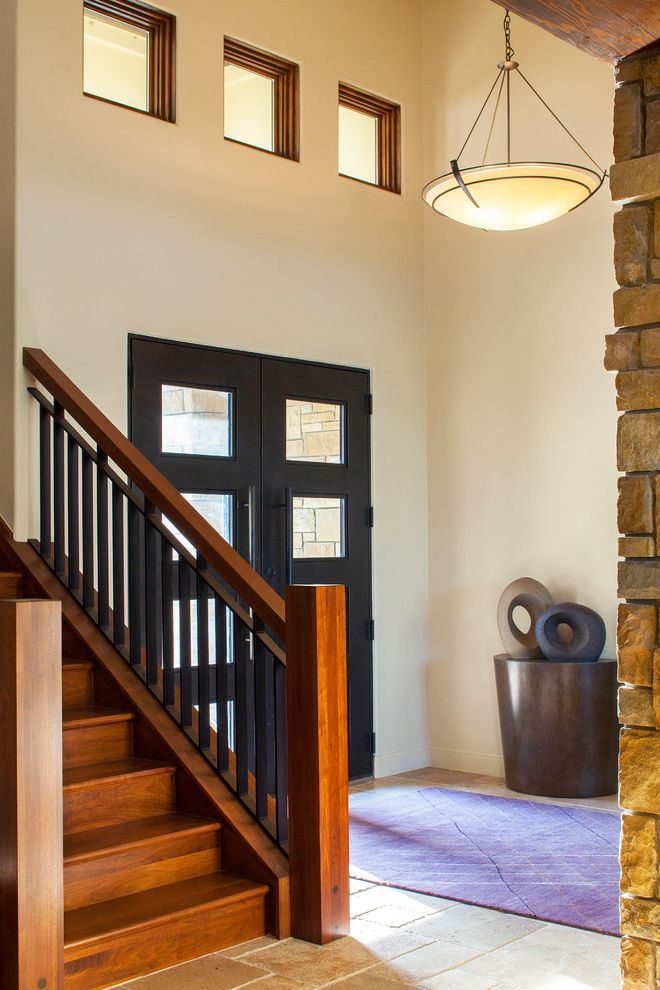 Hubbarton Forge with Transitional Entry Also Area Rug Beige Painted Wall Black Banister Clerestory Windows Glass Panel Double Doors Neutral Colors Pendant Light Sculpture Stacked Stone Tall Ceiling Tile Floor Wood Handrail Wood Staircase