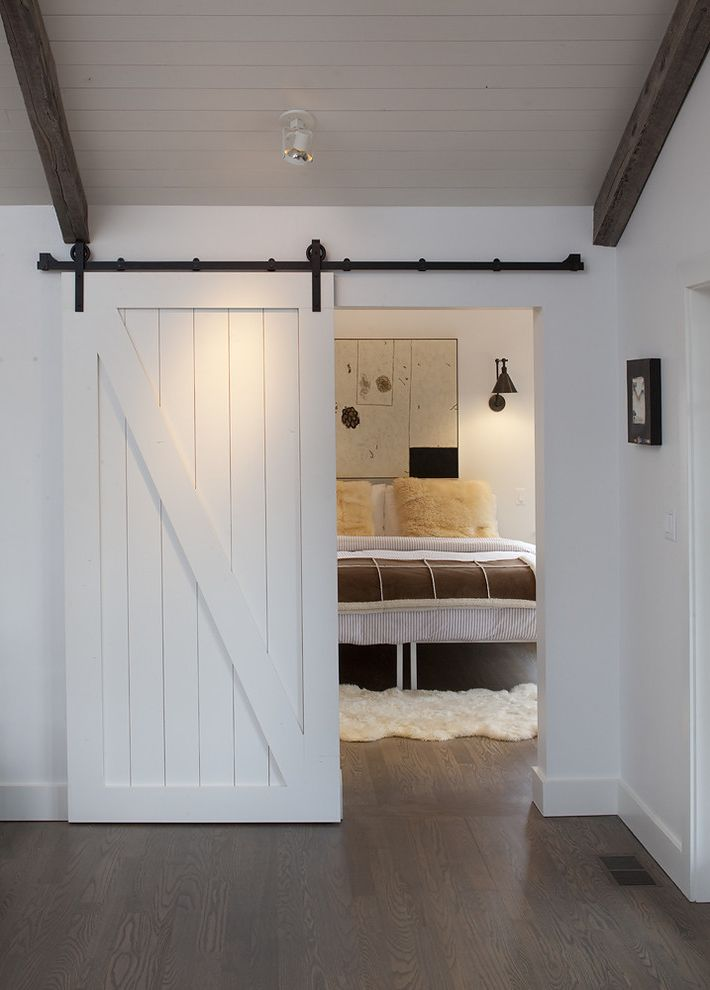 Indoor Barn Doors   Farmhouse Bedroom Also Barn Door Baseboards Ceiling Lighting Dark Floor Exposed Beams Neutral Colors Sliding Doors Wall Art Wall Decor White Wood Wood Ceiling Wood Flooring Wood Trim