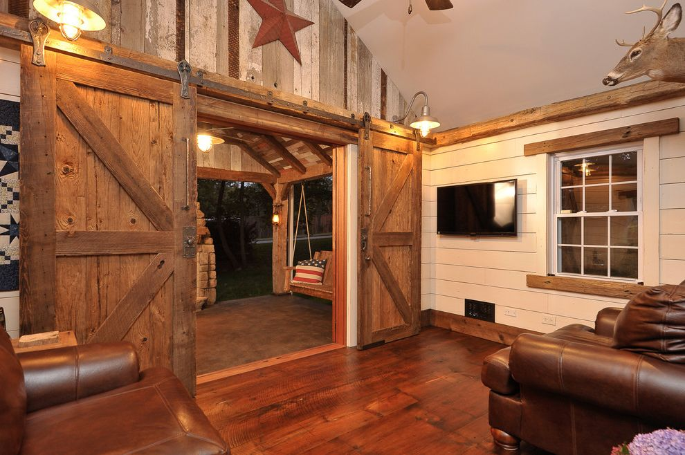 Indoor Barn Doors   Rustic Family Room  and Americana Barn Lighting Brown Leather Lintel Porch Swing Quilt Rustic Doors Salvaged Wood Sliding Barn Doors Stars and Stripes Tv Vaulted Ceiling Wood Beams Wood Floor Wood Paneling