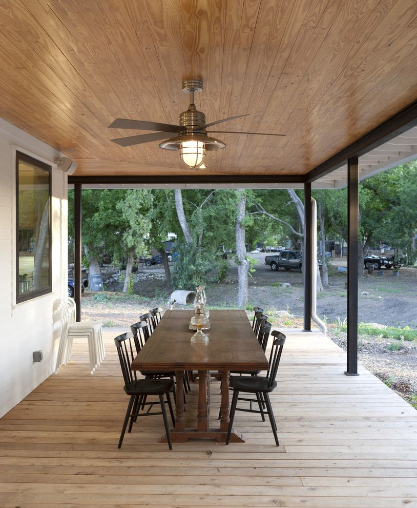Industrial Style Ceiling Fans   Farmhouse Porch  and Ceiling Fan Covered Porch Deck Eaves Open Porch Outdoor Dining Outdoor Lighting Overhang Patio Furniture Trestle Dining Table Wood Ceiling Wood Paneling Wood Siding Wrap Around Porch