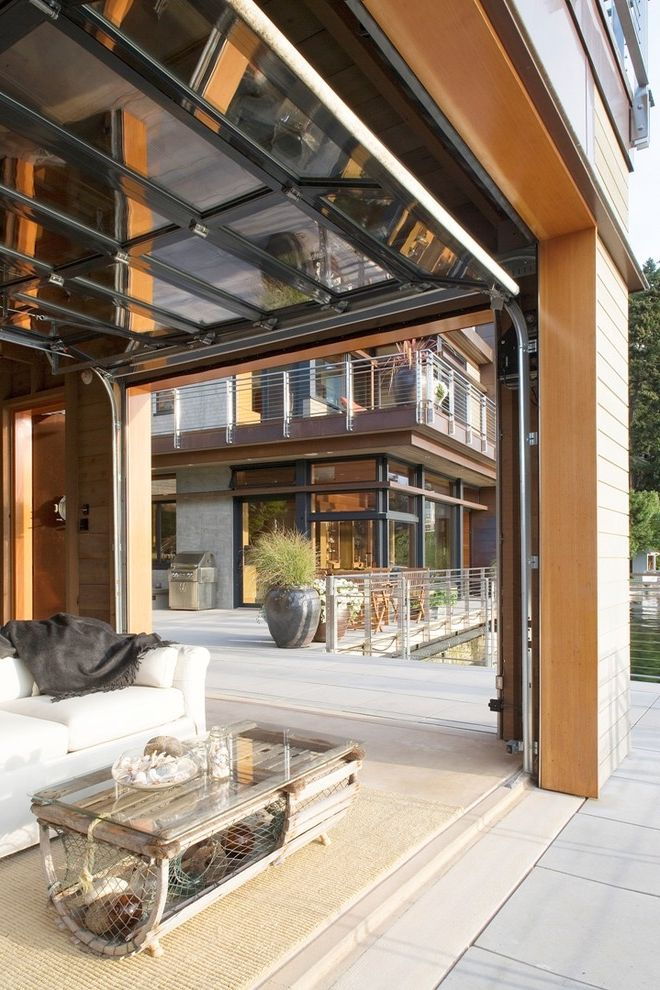 Insulated Glass Garage Doors   Contemporary Patio Also Boathouse Cable Railings Dark Gray Throw Garage Door Windows Grill Potted Plants Rustic Coffee Table Sea Shell Coffee Table Sea Shells White Sofa Wood Siding Wood Slats