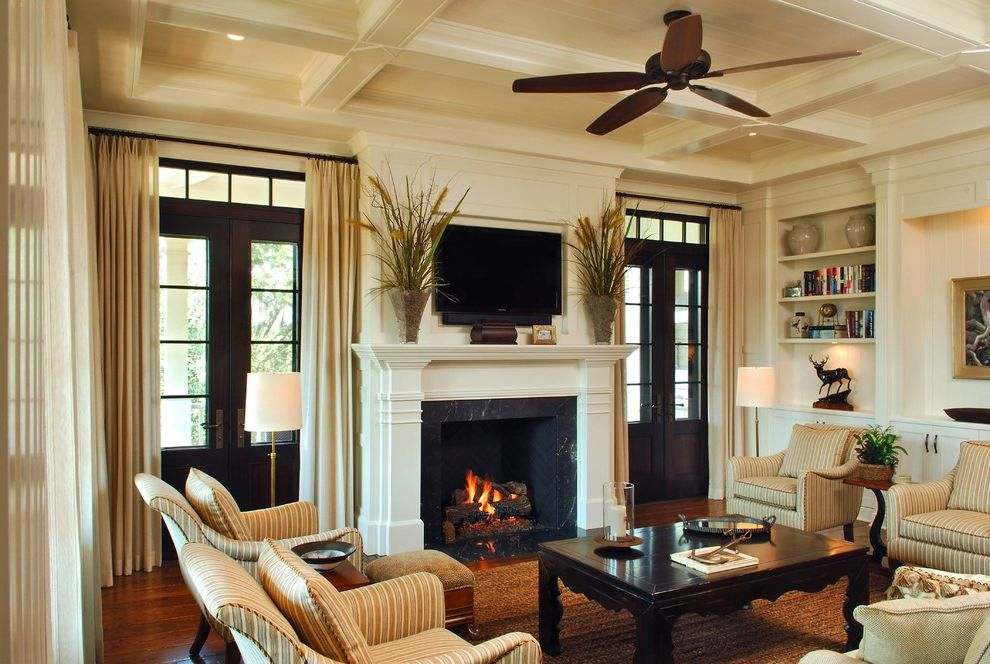 Interior Designers Charleston Sc with Traditional Family Room and Built in Cabinetry Built in Shelving Ceiling Fa Curtains Dark Stained Wood Dark Wood Floor Doubel Doors Fireplace Lighting Living Room Moudling White Mantel Wood Beaming Wood Floors