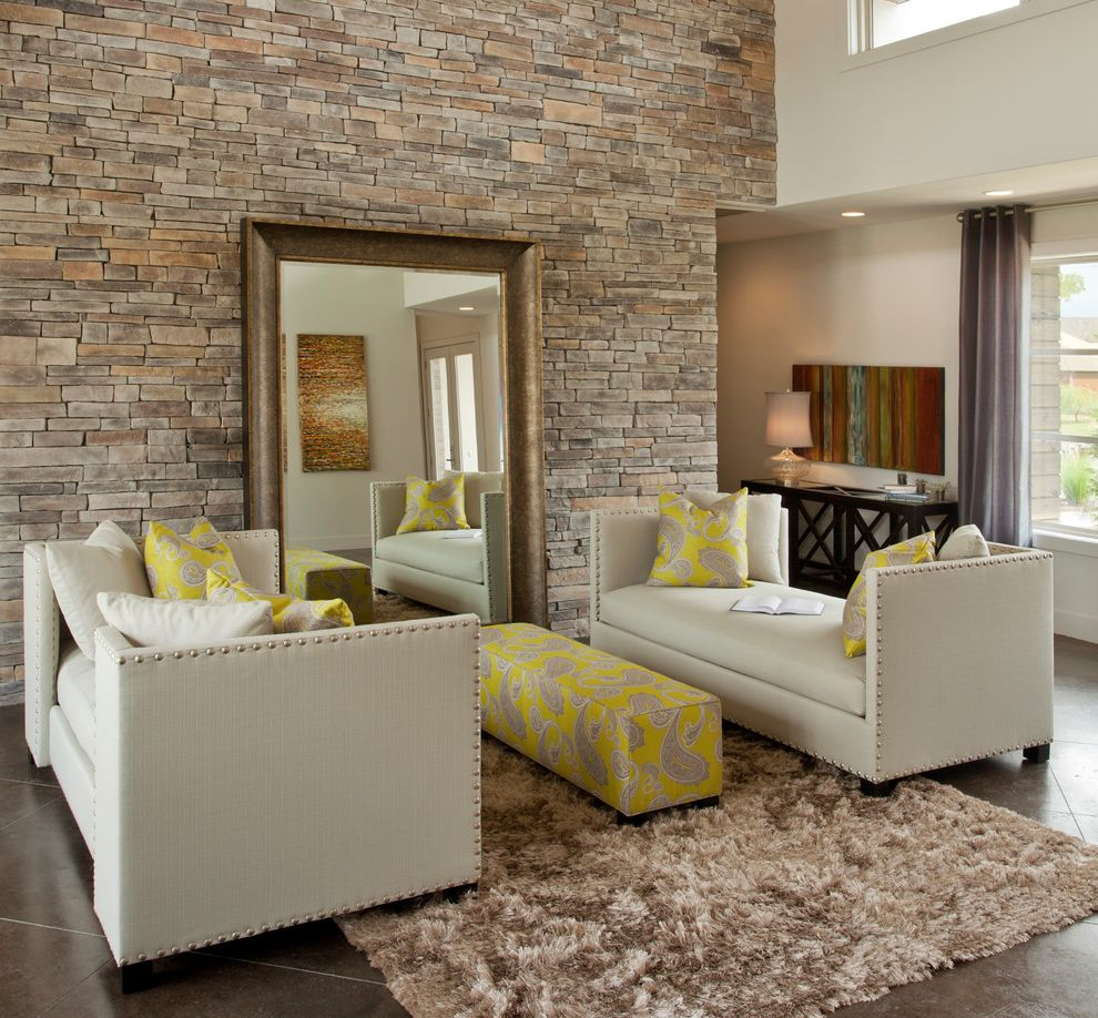 Iometro with Eclectic Living Room  and Area Rug Artwork Brown Day Beds Nail Head Detail Ottoman Stacked Stone Stone Wall Tall Ceilings Tile Floor Wood Framed Mirror Yellow