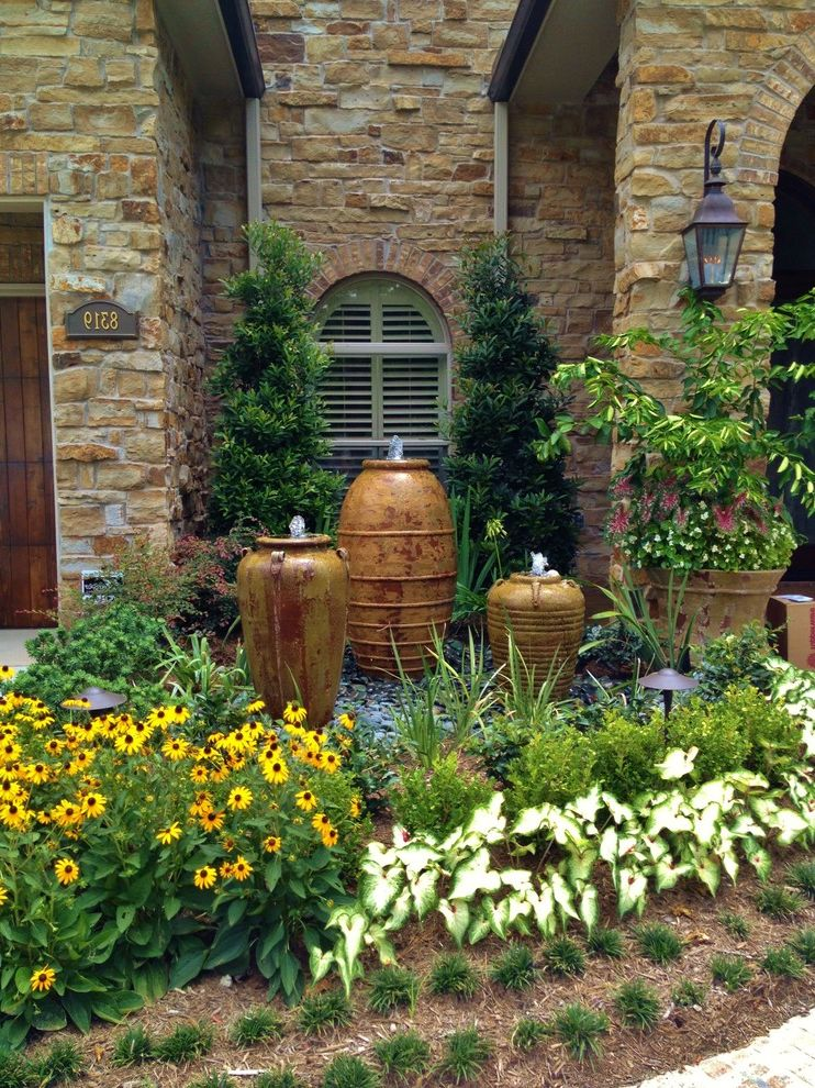 Japanese Blueberry Tree   Mediterranean Landscape  and Annuals Arch Window Bark Mulch Boxwood Bulbs Entry Fountains Garden Perennial Plants Pots Pottery Sconce Shrub Stone Stone Exterior Tree Water Feature Yellow Flowers