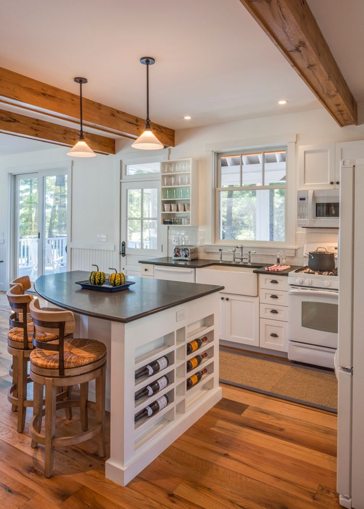 John Moore Plumbing with Farmhouse Kitchen Also Black Counters Breakfast Bar Built in Wine Rack Eat in Kitchen Exposed Beams Kitchen Island Kitchen Island Lighting Post and Beam Reclaimed Timber Reclaimed Wood Floors White Kitchen Wood Bar Stools
