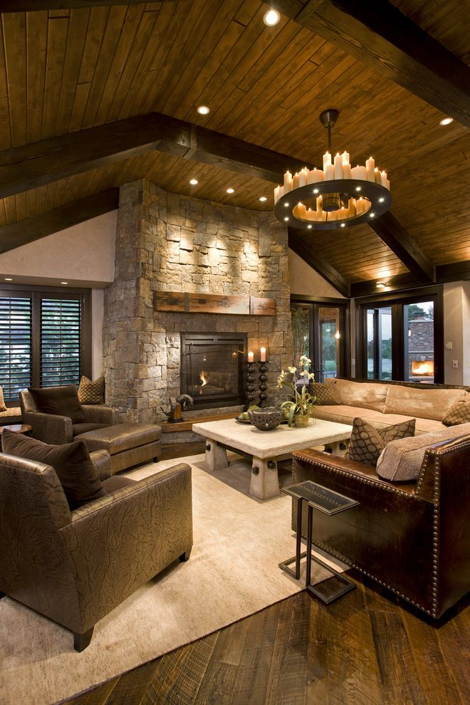 Jon Van Salon with Rustic Family Room  and Area Rug Ceiling Lighting Dark Floor Exposed Beams Fireplace Mantel Leather Armchair Leather Sofa Recessed Lighting Round Chandelier Sloped Ceiling Stone Fireplace Surround Vaulted Ceiling Wood Flooring