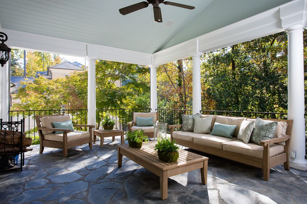 Jonathan Lewis Furniture   Traditional Porch  and Beige Cushions Blue Ceiling Blue Outdoor Pillows Columns Covered Outdoor Areas Metal Railing Outdoor Ceiling Fan Outdoor Furniture Outdoor Seating Area Stone Patio Stone Tile Floor Wooden Patio Furniture