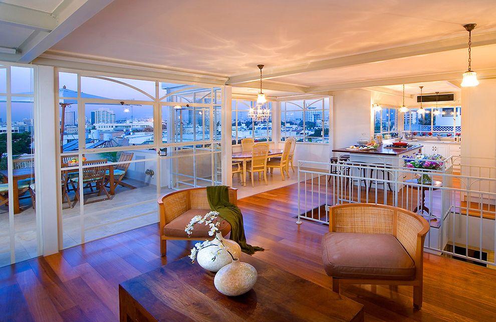 Kempas Hardwood Flooring with Contemporary Living Room  and Cane Corner Chairs Hardwood Floors Indoor Outdoor Large Windows Open Floor Plan Pendant Lights White Railing Wood Coffee Table