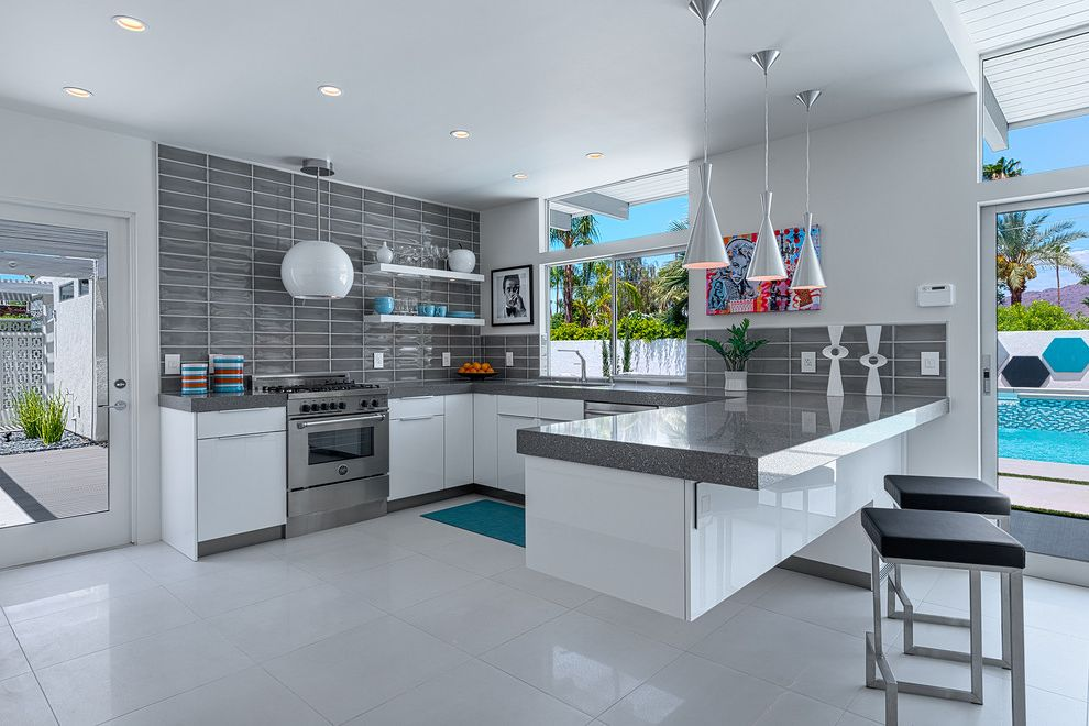 Ketchum Kitchens with Midcentury Kitchen Also Black Bar Stools Blue Area Rug Dropped Ceiling Floating Peninsula Floating Shelves Glass Door Globe Vent Hood Gray Countertop Recessed Lighting Silver Pendant Lights White Flooring