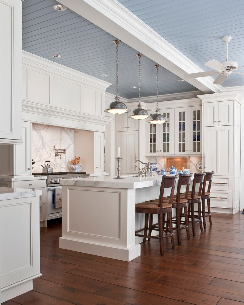 Kitchen Design Stores Near Me   Traditional Kitchen Also Ceiling Fan Counter Stools Frame and Panel Cabinets Hood Kitchen Island Light Blue Marble Backsplash Marble Counters Pendant Lights Pot Filler Rush Seats Tongue and Groove Paneling Wood Floor