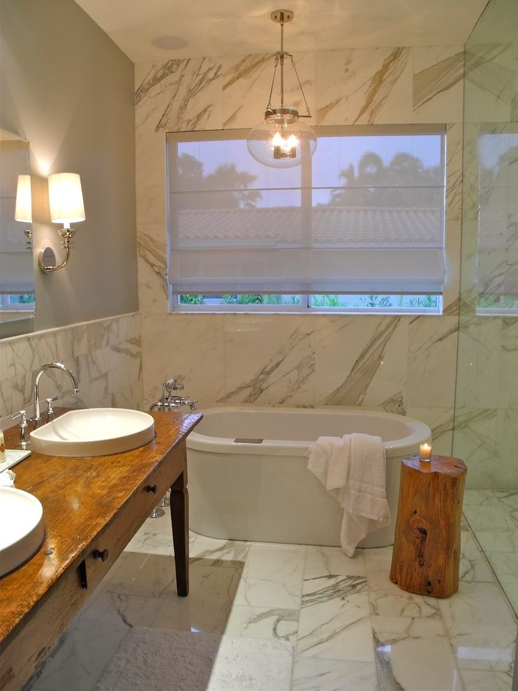 Kohler K 2210 0   Contemporary Bathroom  and Bath Calcutta Gold Gray Marble Oval Tub Pendant Light Rustic Vanity Sinks Soaker Tub Stool Tiled Floor Tub Wall Sconce Wood Vanity