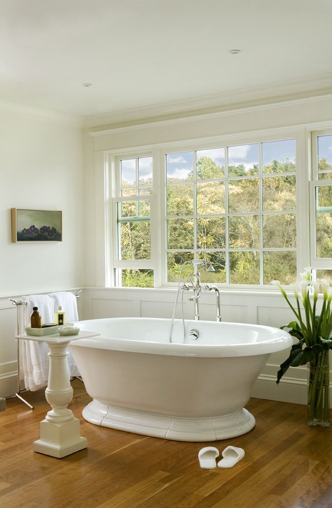 Kohler Tub Surround with Traditional Bathroom  and Floor Mount Tub Filler Frame and Panel Freestanding Tub Pedestal Table Towel Stand Wainscot White Painted Wood Wood Floor