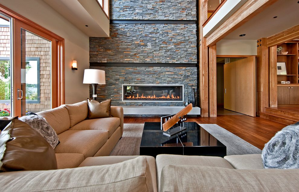 Lady Justice Blindfolded with Contemporary Living Room Also Black Lacquer Coffee Table Cable Rails Glass Doors High Ceiling Large Beams Large Sectional Loft Stacked Stone Fireplace Tan Couch Tan Sofa Wood Accents