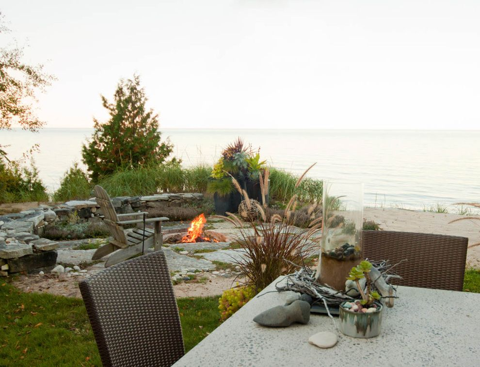Lakeside Natural Medicine with Beach Style Landscape  and Adirondack Chairs Beach Centerpiece Coastal Grass Grasses Lawn Outdoor Dining Outdoor Fire Pit Patio Furniture Potted Plants Seat Wall Stone Wall Turf View Waterfront