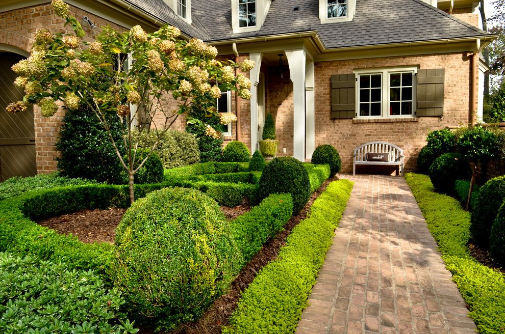 Landscaping Anderson Sc   Traditional Landscape  and Arched Garage Door Brick Exterior Brick Pathway Brick Siding Brick Walkway Brown Shutter Dark Brown Garage Door Exterior French Country Hedges Mulch Shrubs Tree White Beam White Post Wood Outdoor Bench