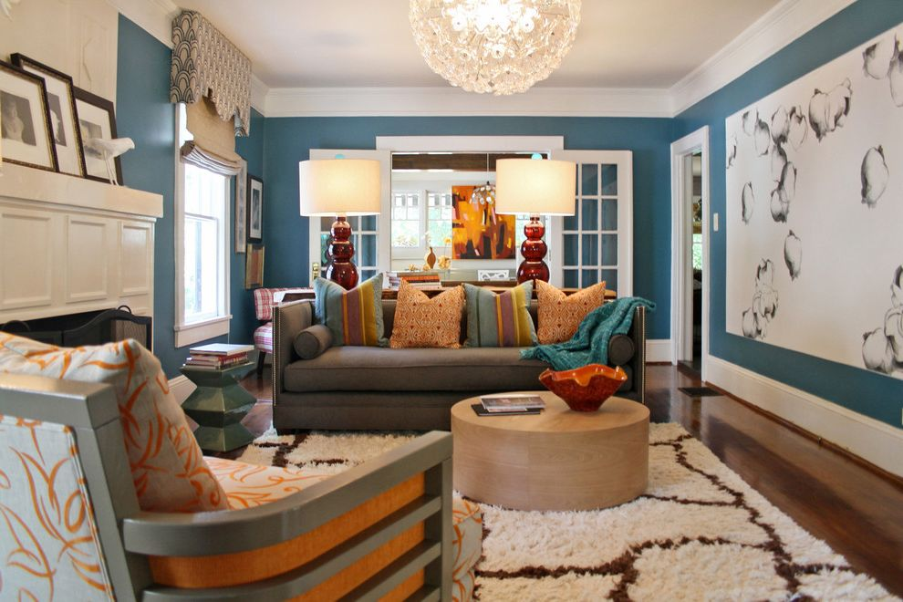 Large Prints for Walls with Transitional Spaces Also Blue Walls Contemporary Sofa Fireplace Mantel French Doors Glass Floral Light Large Artwork Moroccan Rug Orange and Blue Round Wood Coffee Table Valance Venetian Light White Trim Wide Trim