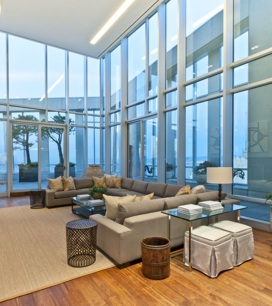 Large Sectional Sofa with Ottoman   Contemporary Family Room  and Area Rug Corner Windows Decorative Pillows End Table Glass Walls High Ceilings Natural Rug Sectional Sofa Side Table Sofa Table Tall Ceiling Tan Couch Throw Pillows Wood Flooring
