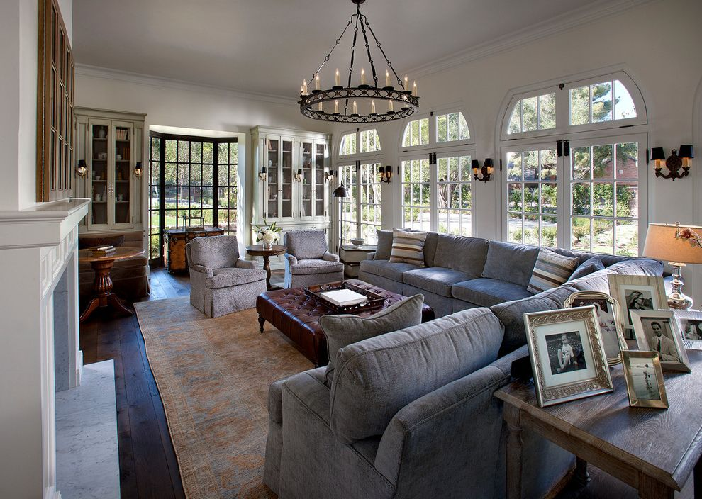 Large Sectional Sofa with Ottoman   Traditional Living Room Also Black Chandelier Brown Leather Ottoman Crown Molding Double Sconces Gray Sectional Sofa Persian Rug Round Chandelier Silver Frames Square Ottoman Striped Pillows Transom Windows