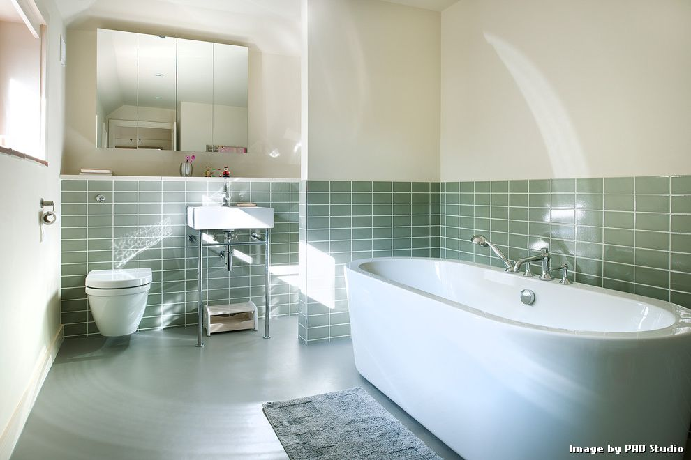 Linoleum Floor Tiles with Contemporary Bathroom and Exposed Sink Pipes Foot Stool Gray Bath Mat Green Glass Tiles Half Tiled Wall Mirrored Cabinet Doors Recessed Wall Recessed Window Rectangular Sink White Baseboards White Freestanding Tub