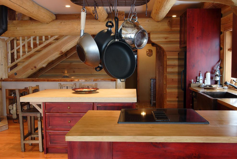 Log Cabin Stain with Rustic Kitchen  and Butcher Block Counter Stools Knotty Pine Log Home Log Walls Pot Rack Red Stained Kitchen Cabinets Wood Beams Wood Counters Wood Floor