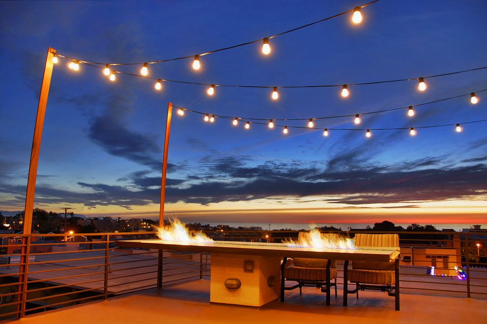 Low Voltage Deck Post Lights with Modern Deck  and Balcony Fire Patio Table Fire Pit Table Fire Table Metal Beam Metal Post Metal Railing Outdoor Outside Roof Deck Rooftop Deck String Lighting String Lights Striped Patio Chairs Sunset View