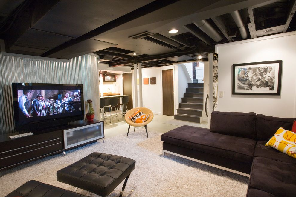 Lowering Basement Floor Cost   Industrial Basement  and Artwork Bar Basement Renovation Black Ceiling Black Leather Black Sofa Cgi Corrugated Galvanized Iron Counter Stools Exposed Ducting Floor Joists Media Room Seating Area Sectional Area Rug