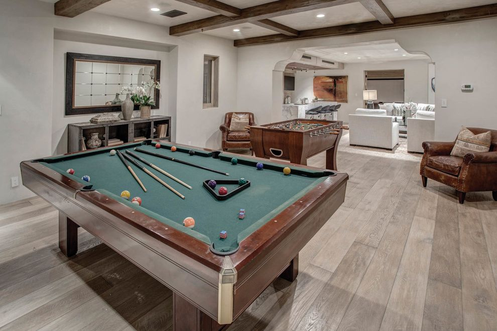 Lowering Basement Floor Cost   Mediterranean Basement  and Beamed Ceiling Brown Armchair Dark Wood Beams Foosball Table Framed Mirror Pool Table