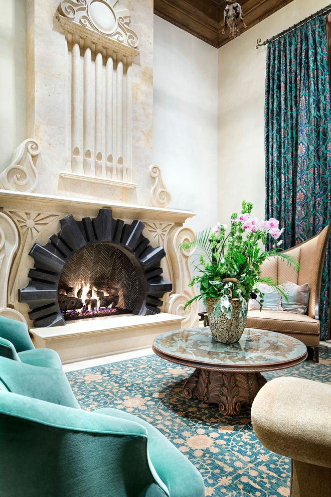 Mad Hatter Fireplace   Mediterranean Living Room Also Carved Fireplace Mantel High Ceilings Ornate Purple and Green Curtains Raised Fireplace Hearth Round Coffee Table Statement Fireplace Turquoise Armchair Turquoise Floral Area Rug
