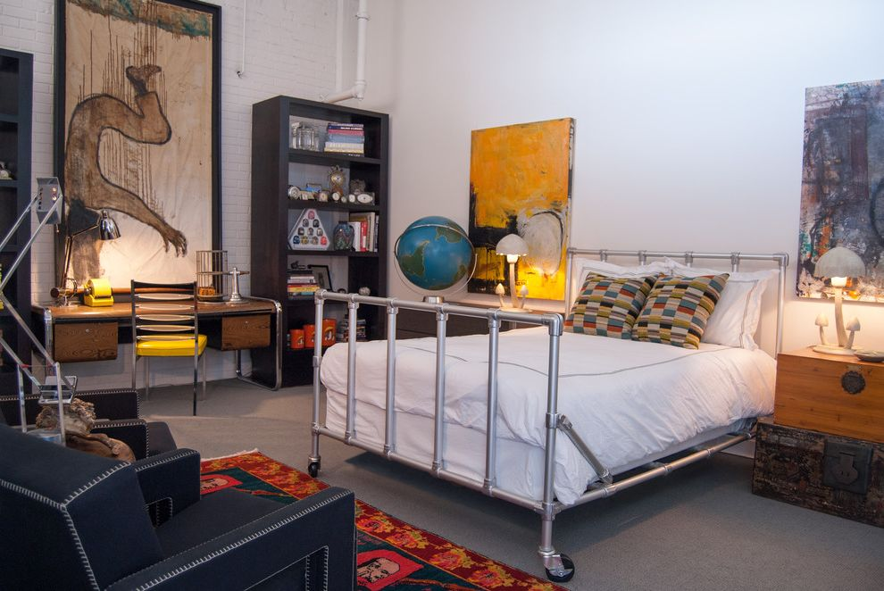 Masculine Bed Frames with Industrial Bedroom  and Armchair Art Bed Bed on Wheels Brick Wall Desk Grey Armchair Shelves Speedrail Trunk Yellow Chair