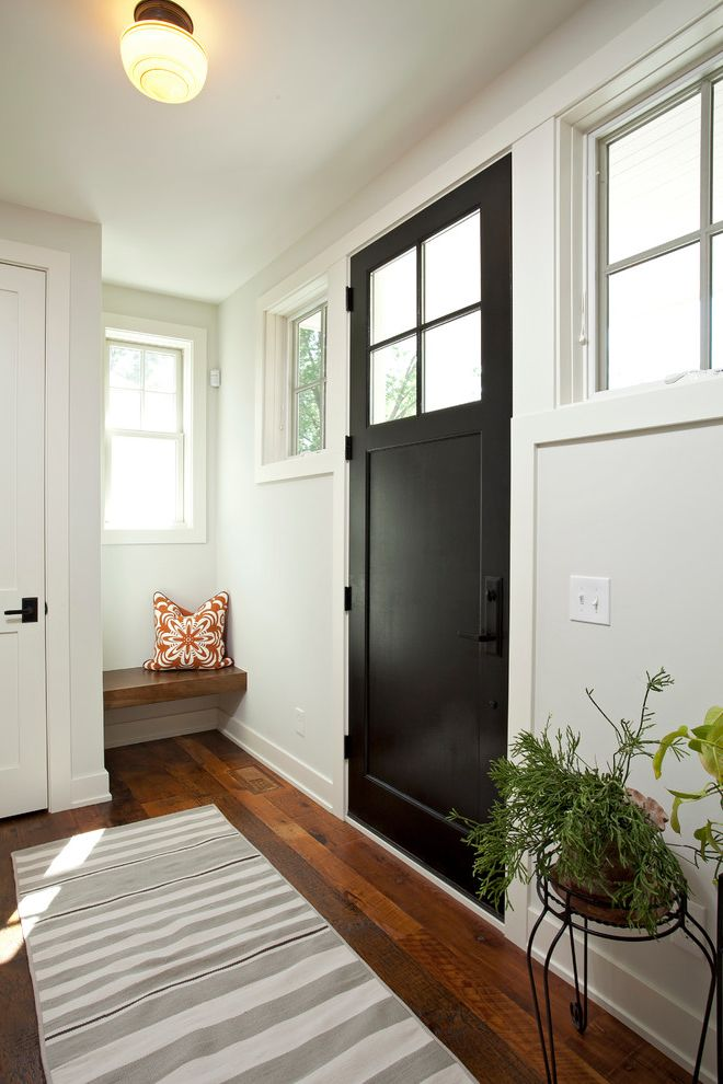 Matte Black Door Handles   Farmhouse Entry  and Black Door Built in Bench Dark Hardwood Floor Gray and White Rug Gray and White Runner Plant Stand Semi Flush Ceiling Light Shaker Door Square Window Striped Rug Striped Runner White Walls Window Panes