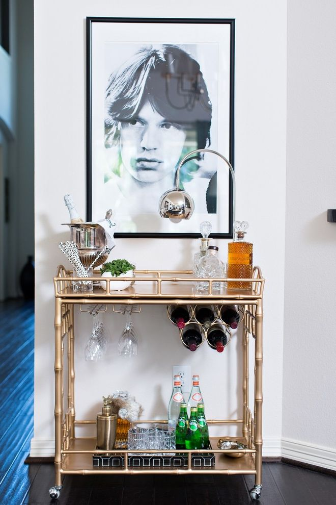 Media Cart on Wheels with Transitional Home Bar  and Bar Cart on Casters Chrome Table Lamp Drinks Cabinet Framed Black and White Photo Gold Bamboo Bar Cart Hanging Wine Glasses Mick Jagger Poster Rolling Stones Wine Bottle Rack