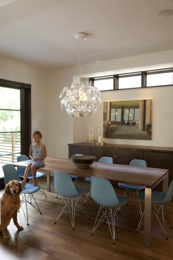 Metal Drafting Table   Contemporary Dining Room  and Artwork Blue Plastic Dining Chairs Chandelier Dark Wood Trim Eames Chair Glass Door Metal Table Legs Wood Dining Table Wood Flooring Wood Sideboard