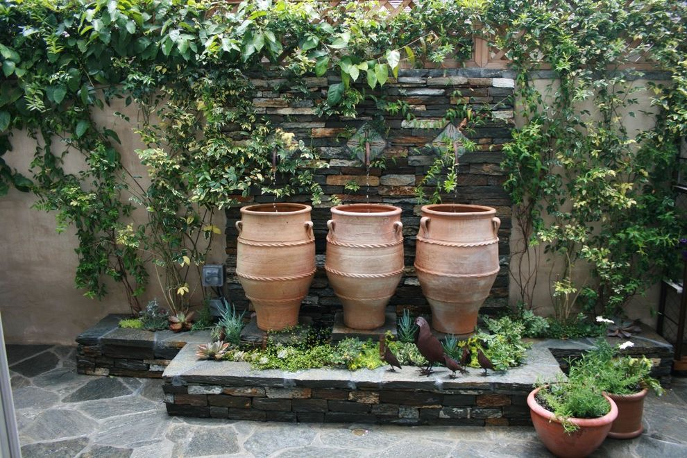 Mexican Water Jug with Beach Style Patio  and Climbing Plants Container Plants Fountain Garden Art Pavers Potted Plants Stone Paving Terracotta Pots Water Feature