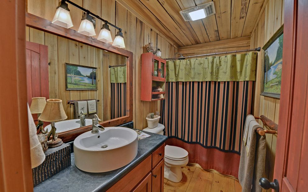 Mile North Hotel with Traditional Bathroom  and Charcoal Counter Dragonfly Shower Curtain Log Cabin Rustic Wood Walls Single Vanity Storage Above Toilet Striped Shower Curtain Wide Plank Floor Wood Ceiling Wood Mirror Frame