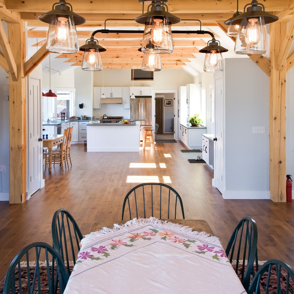 Mission Style Light Fixtures with Traditional Kitchen and Area Rug Dining Room Gray Walls Kitchen Knotty Pine Spindle Chairs Lanterns Lighting Open Floor Plan Open Plan Table Cloth White Baseboard White Cabinets Wood Beams Wood Floor